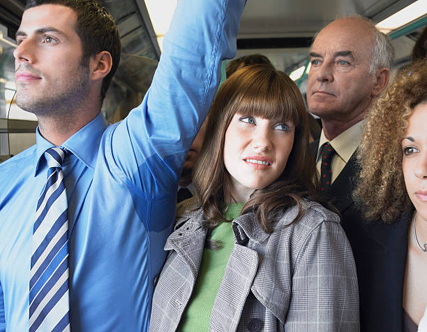 Female Commuter Standing by Man's Wet Armpit In Train stock photo