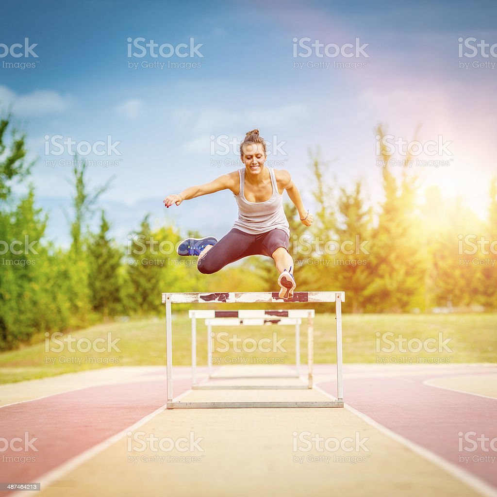 Female competitor jumping the steeplechase obstacle stock photo