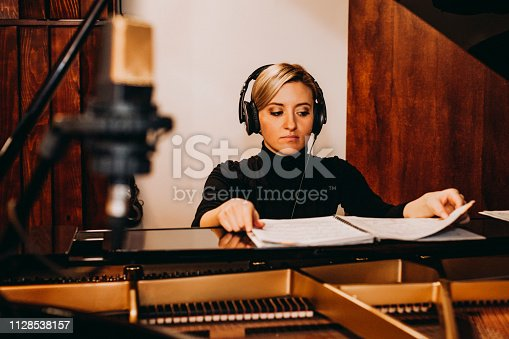 Female composer playing piano at sound recording studio.