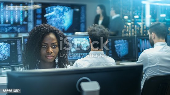 istock Female Computer Engineer Works on a Neural Network/ Artificial Intelligence Project with Her Multi-Ethnic Team of Specialist. Office Has Multiple Screens Showing 3D Visualization. 866661052