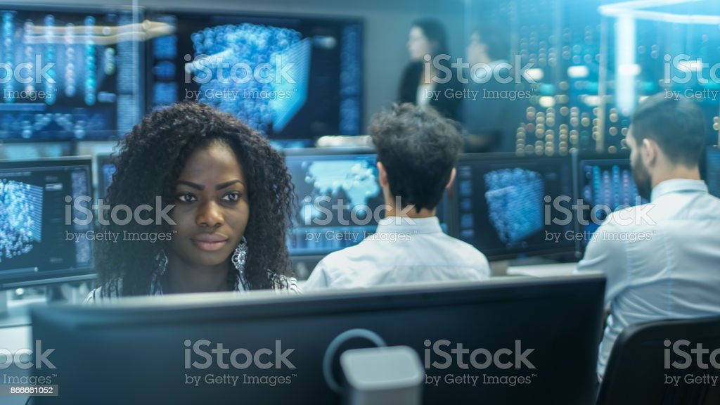 Female Computer Engineer Works on a Neural Network/ Artificial Intelligence Project with Her Multi-Ethnic Team of Specialist. Office Has Multiple Screens Showing 3D Visualization. stock photo