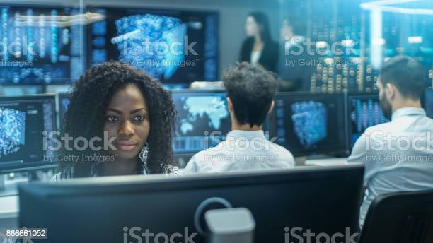 Female Computer Engineer Works On A Neural Network Artificial Intelligence Project With Her Multiethnic Team Of Specialist Office Has Multiple Screens Showing 3d Visualization Stock Photo - Download Image Now