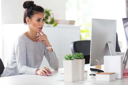 Female Computer Programmer Looking Worried While Working Stock Photo - Download Image Now