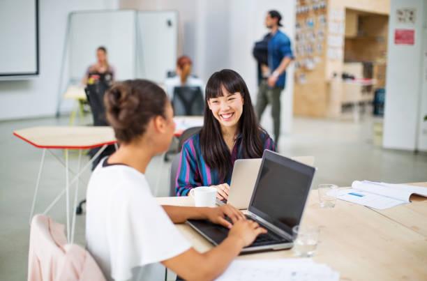 オフィスで一緒に働く女性プログラマー - 談笑する ストックフォトと画像