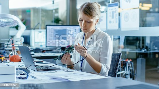 968289374istockphoto Female Computer Scientists Connects Circuit Board to Her Laptop and Starts Programming it. She Works in the Technologically Advanced Laboratory. 968289526