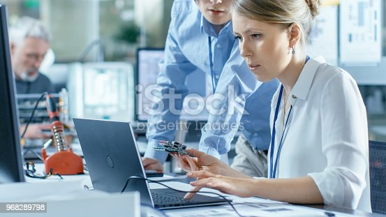 968289374istockphoto Female Computer Scientists Connects Circuit Board to Her Laptop and Starts Programming it. She Works in the Technologically Advanced Laboratory. 968289798