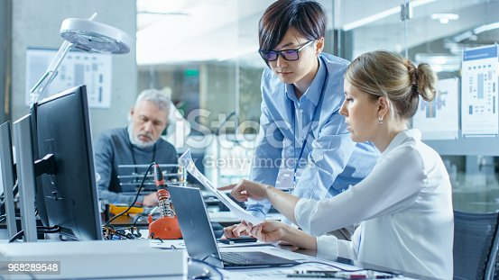 968289374istockphoto Female Computer Scientists Connects Circuit Board to Her Laptop with Mock-up Green Screen. She Works in the Technologically Advanced Laboratory. 968289548