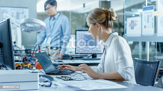968289374istockphoto Female Computer Scientists Connects Circuit Board to Her Laptop with Mock-up Green Screen. She Works in the Technologically Advanced Laboratory. 968303210