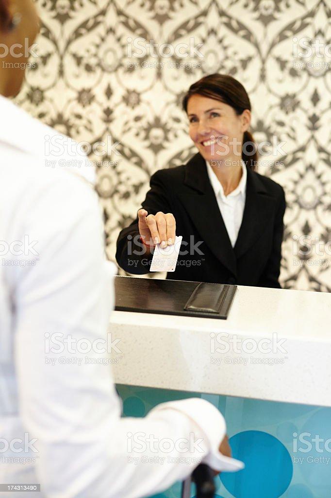 Female concierge handing room key to customer stock photo