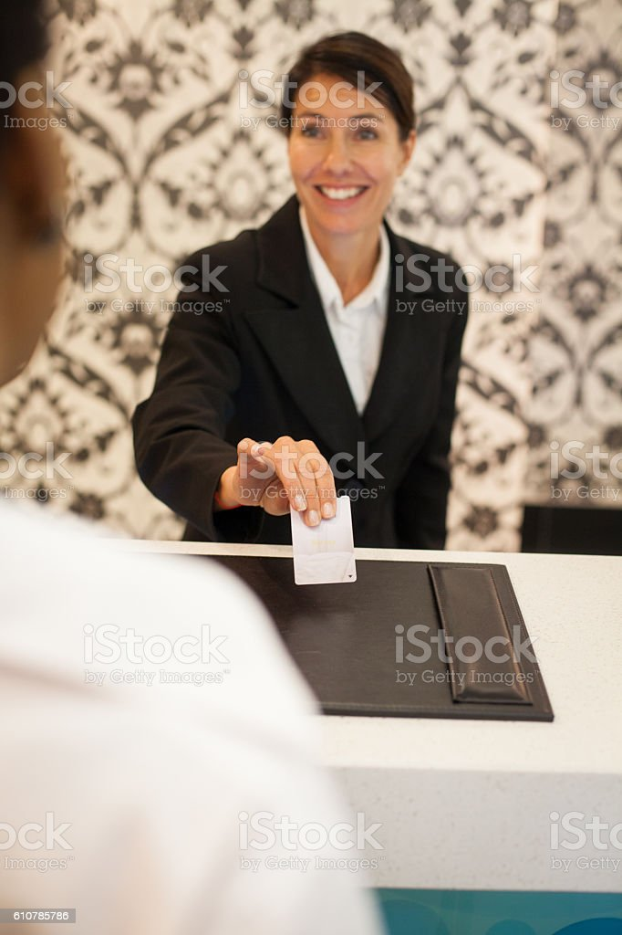 Female concierge handing room key to guest stock photo