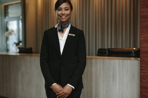 Female concierge ready to welcome guest Portrait of female concierge standing at hotel reception to welcome guest. Female concierge working in hotel. concierge stock pictures, royalty-free photos & images