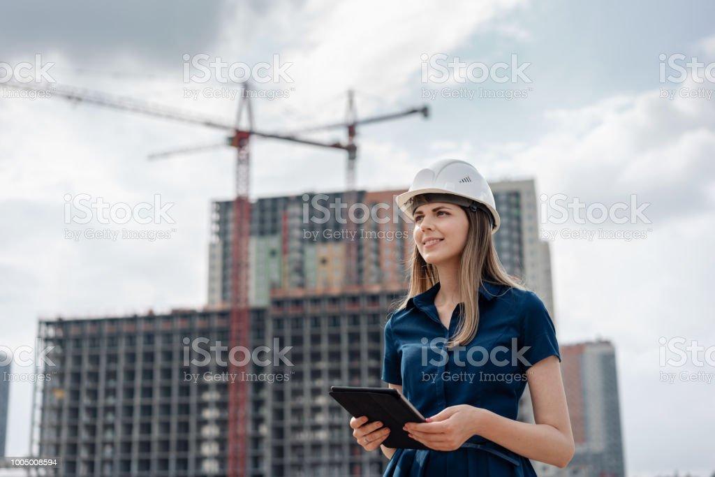 Weibliche Bauingenieur. Architekt mit einem tabletcomputer auf einer Baustelle. Junge Frau auf der Suche, Gebäude Website Ort auf Hintergrund. Baukonzept – Foto