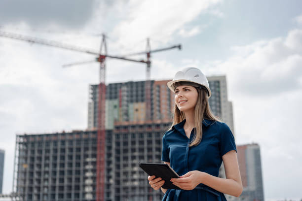 Female construction engineer. Architect with a tablet computer at a construction site. Young Woman looking, building site place on background. Construction concept Female construction engineer. Architect with a tablet computer at a construction site. Young Woman look in camera, building site place background. engineer stock pictures, royalty-free photos & images