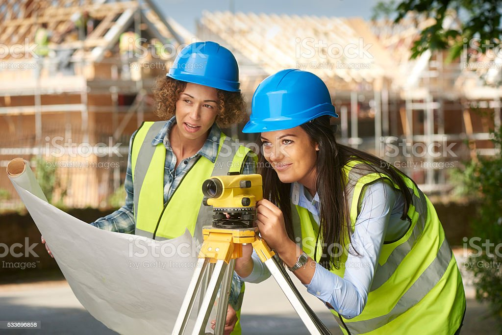 A female site engineer and assistant are out on the housing...