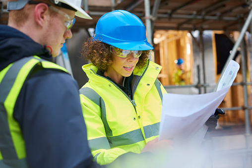 a female construction worker stands on a building site housing development and instructs a co -worker.