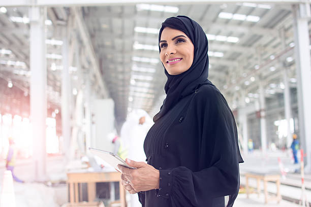 Female Construction Manager is Happy With Construction Confident Arab woman dressed in abaya looking forward while holding a digital tablet. arabic style stock pictures, royalty-free photos & images