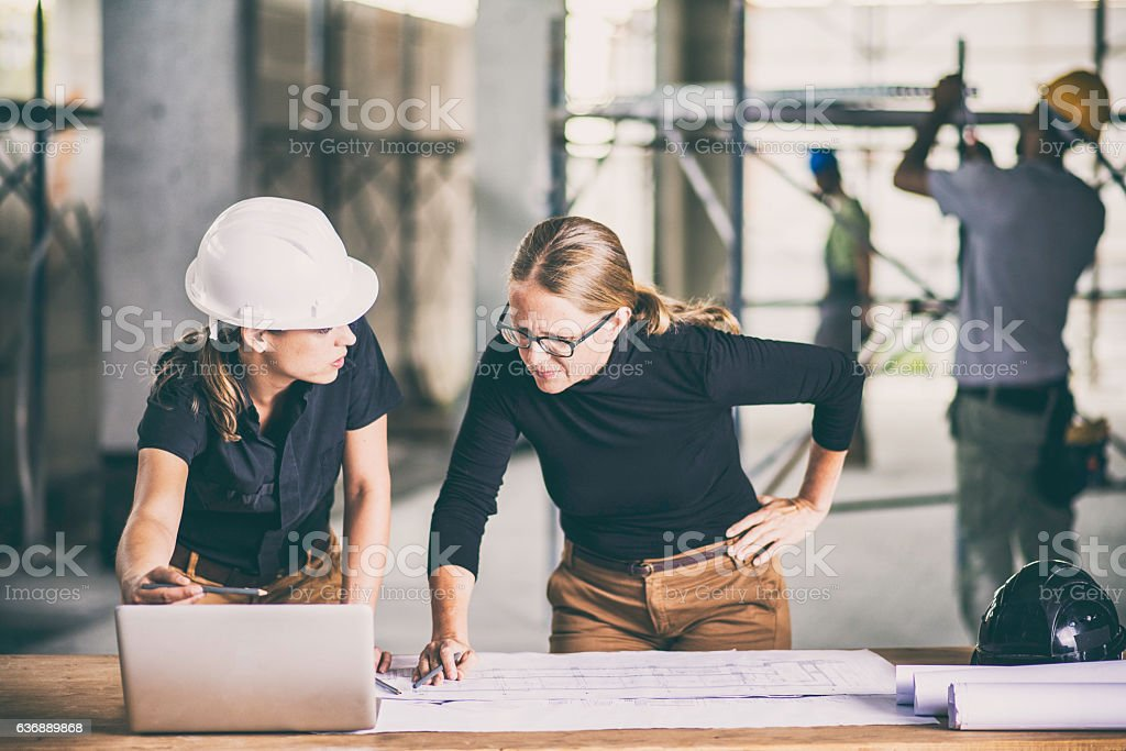 Female construction worker consulting an architect stock photo