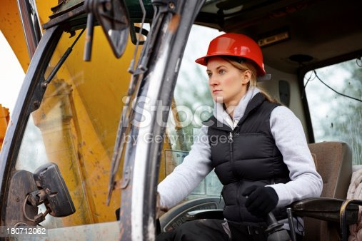 Female construction worker driving an earth mover on a construction site