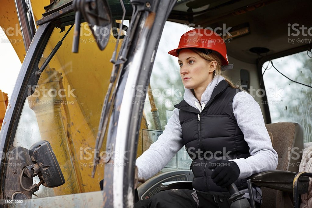 Female construction worker driving an earth mover stock photo
