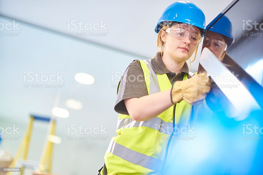 female construction worker fitting handrails stock photo