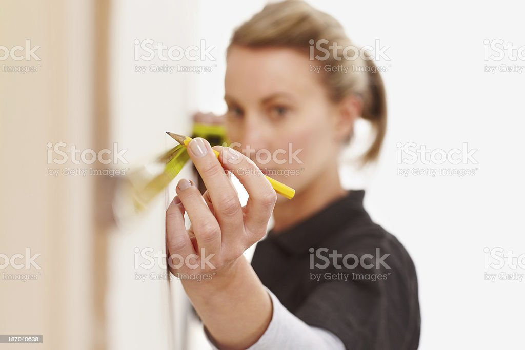 Female construction worker marking distance on wall stock photo