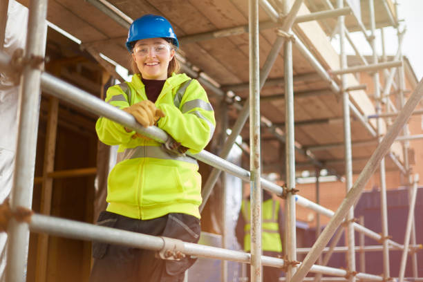 female construction worker portrait a female construction worker stands behind a scaffold and smiles to camera on a building site scaffolding stock pictures, royalty-free photos & images