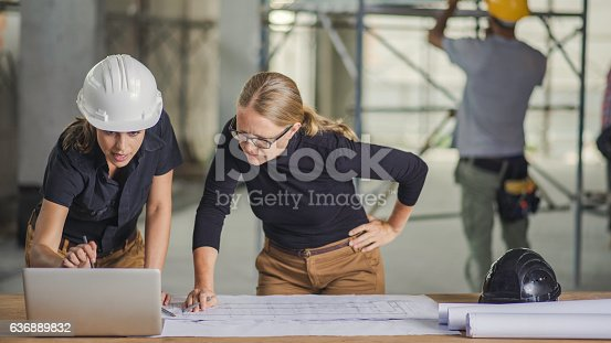 Front view of two women standing by the desk full of blueprints and laptop, construction worker in background.