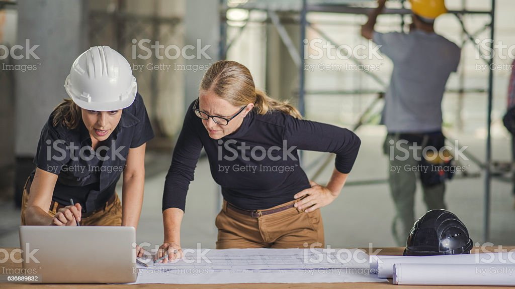 Female constructor and female architect reviewing blueprints stock photo