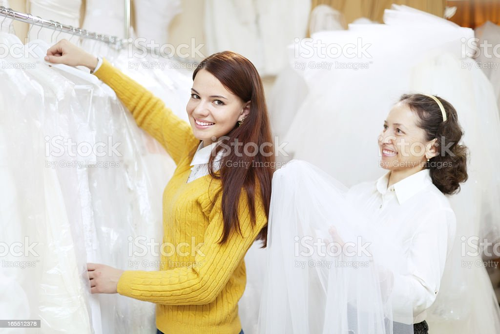 Female consultant helps bride  at shop royalty-free stock photo