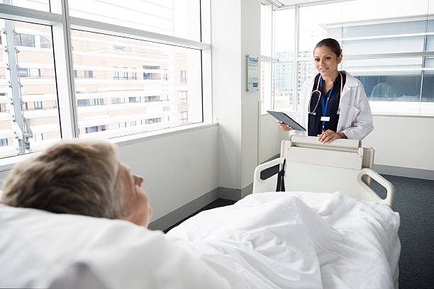 female consultant talking to mature woman in hospital - australian nurses stock photos and pictures