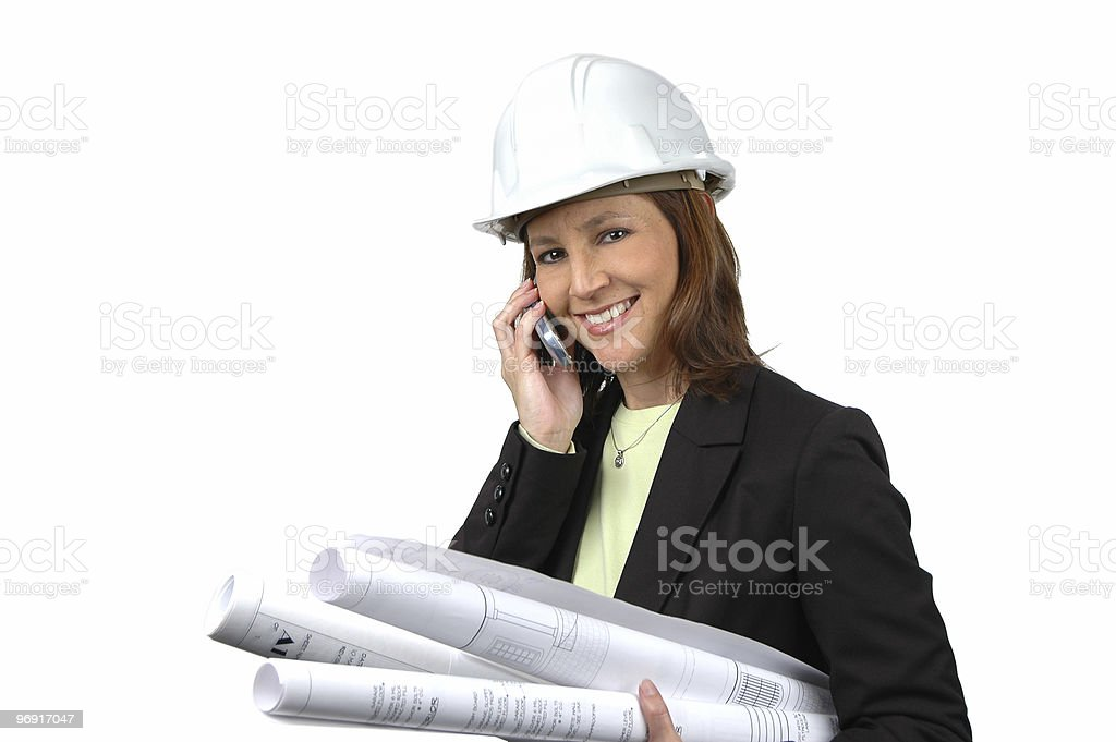 Female contractor on the cell phone holding blue prints royalty-free stock photo