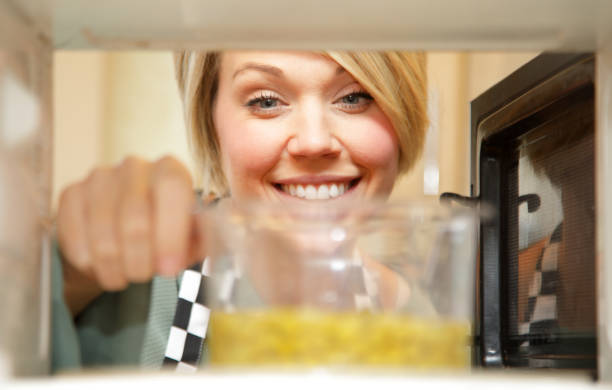 female cook heating food in microwave stock photo