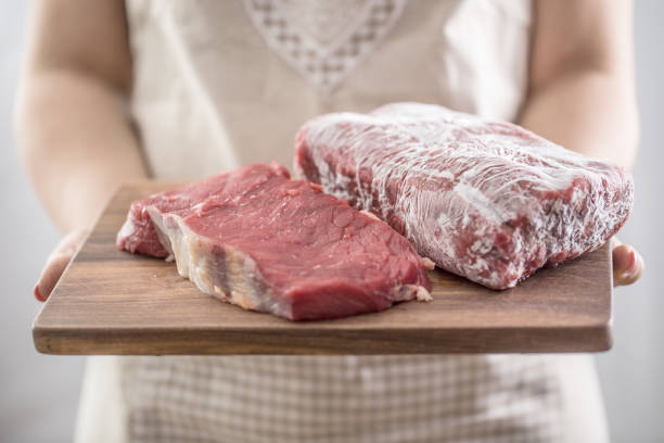 Female cook holding wooden board of raw and frozen beef  meat stock photo