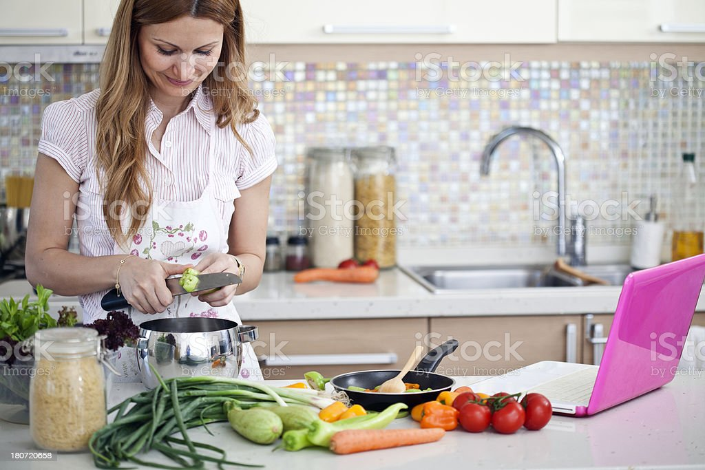 female cooking and looking at laptop in kitchen royalty-free stock photo