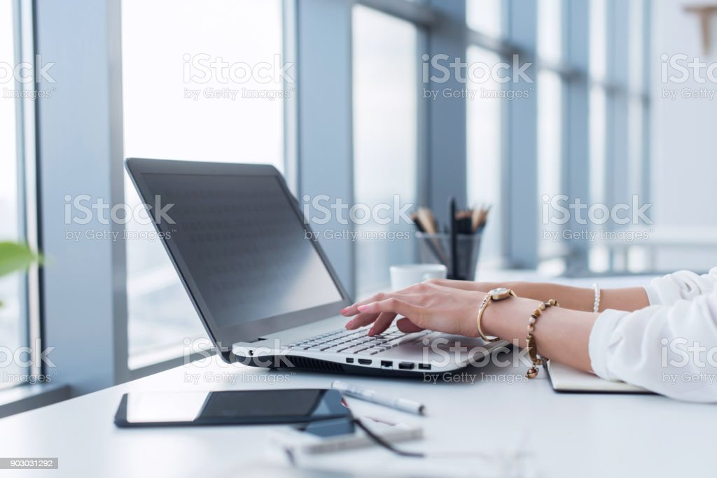 Female copywriter at her workplace, home, writing new text using laptop and Wi-Fi internet connection in the morning. stock photo