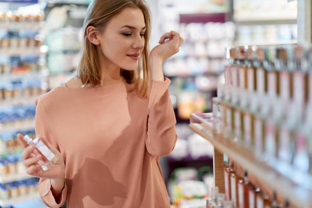 kobieta kostiumy kupuje perfumy w sklepie - perfumowany zdjęcia i obrazy z banku zdjęć
