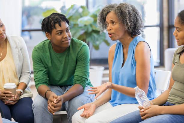consejero femenino informa personas durante la reunión del grupo de apoyo - consejero de la escuela fotografías e imágenes de stock