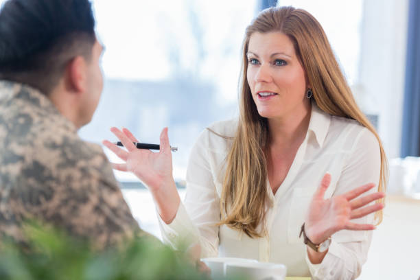 female counselor talks with military veteran - military lifestyle stock pictures, royalty-free photos & images
