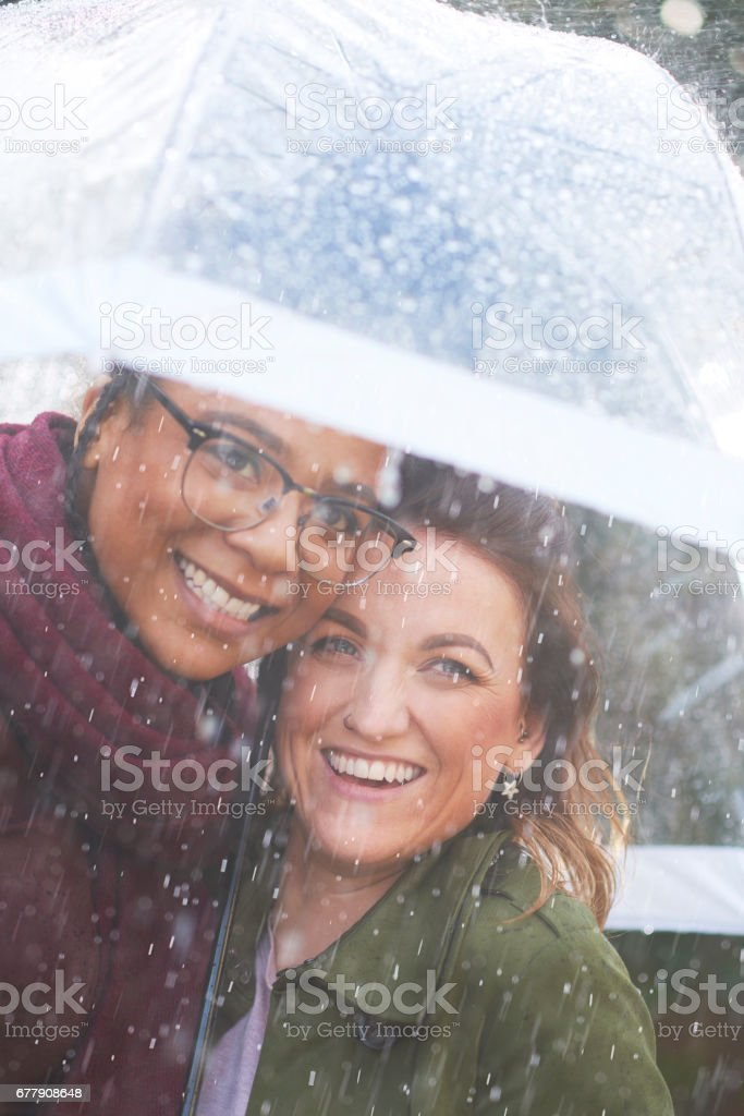 female couple caught out in the rain royalty-free stock photo