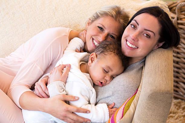 female couple cuddling with their baby son - lesbische stockfoto's en -beelden