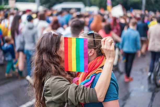 Female couple hiding behind rainbow flag stock photo