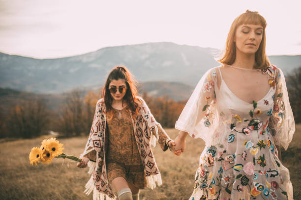 weibliches paar hand in hand - hippie kleider stock-fotos und bilder