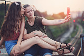Female couple kissing and making selfies.