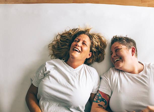 female couple laughing together - lesbische stockfoto's en -beelden