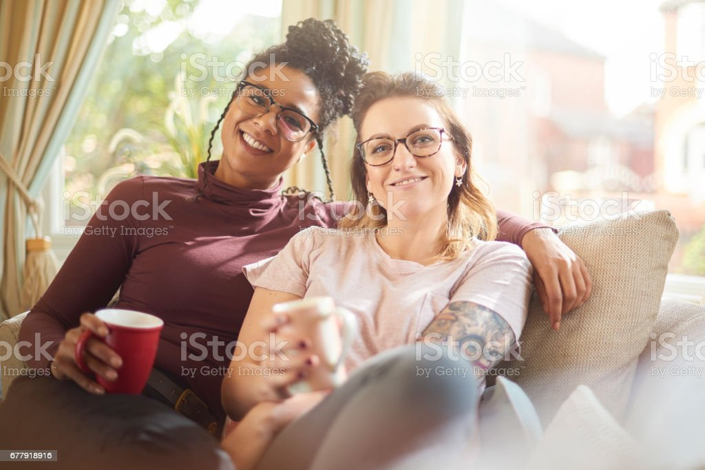 female couple relaxing at home smile to camera royalty-free stock photo