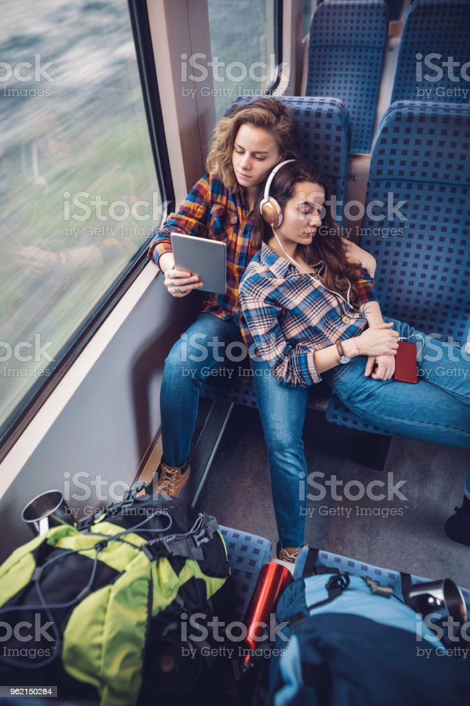 Female couple relaxing with music while travelling by train stock photo