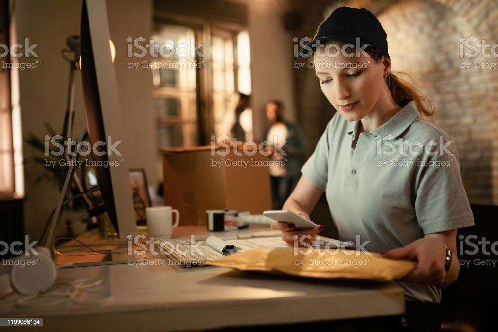 Young deliverer scanning bar code on package with mobile phone while...