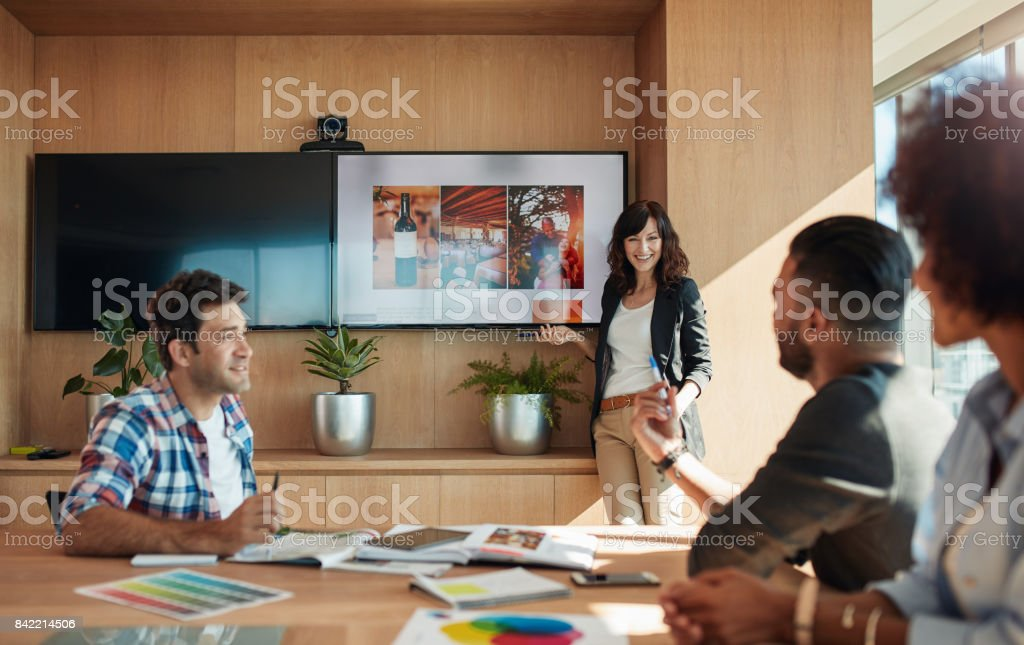 Female coworker making presentation in office stock photo