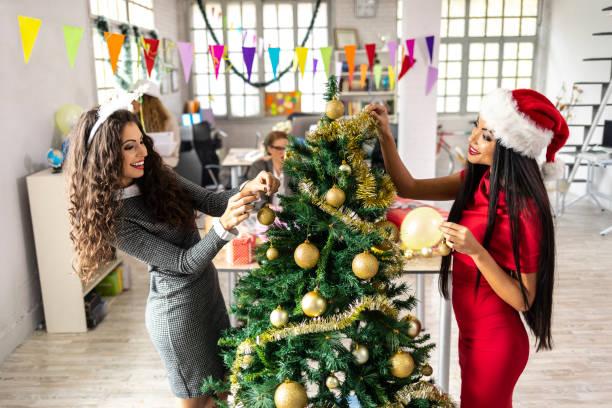 weiblichen mitarbeiter schmücken weihnachtsbaum am arbeitsplatz - frohes neues jahr stock-fotos und bilder