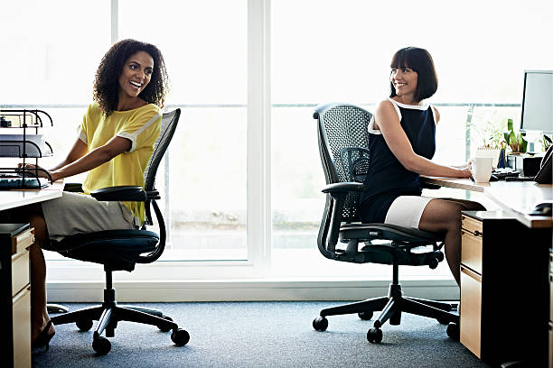 female coworkers laughing - chaise de bureau photos et images de collection